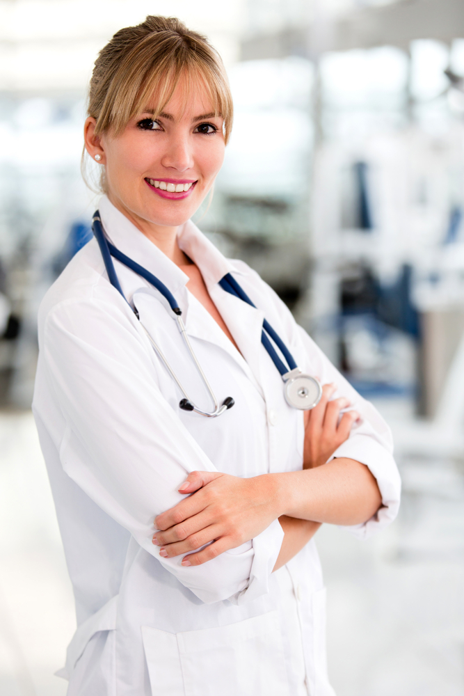 Beautiful female doctor smiling with arms crossed
